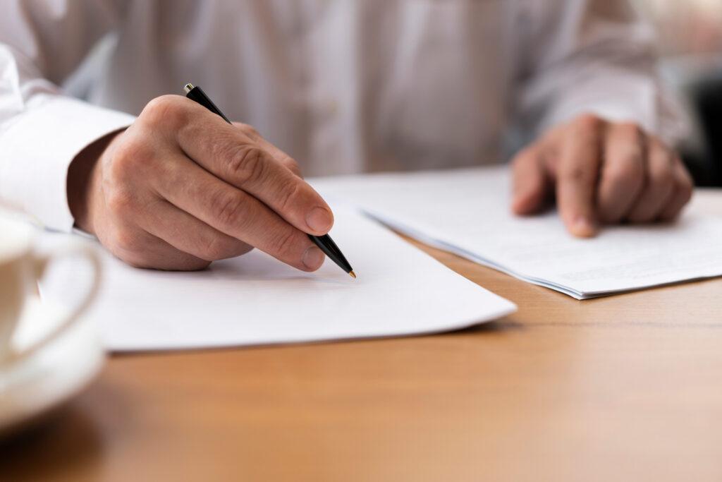 Un uomo con una penna in mano controlla dei documenti