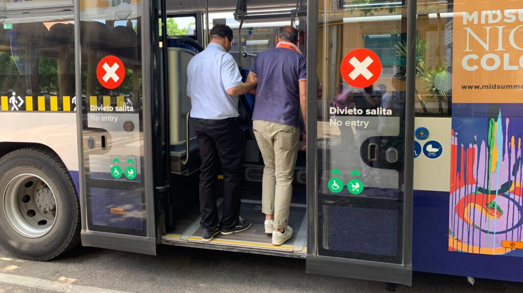 Un autista atv accompagna un suo collega bendato per simulare la salita sull'autobus