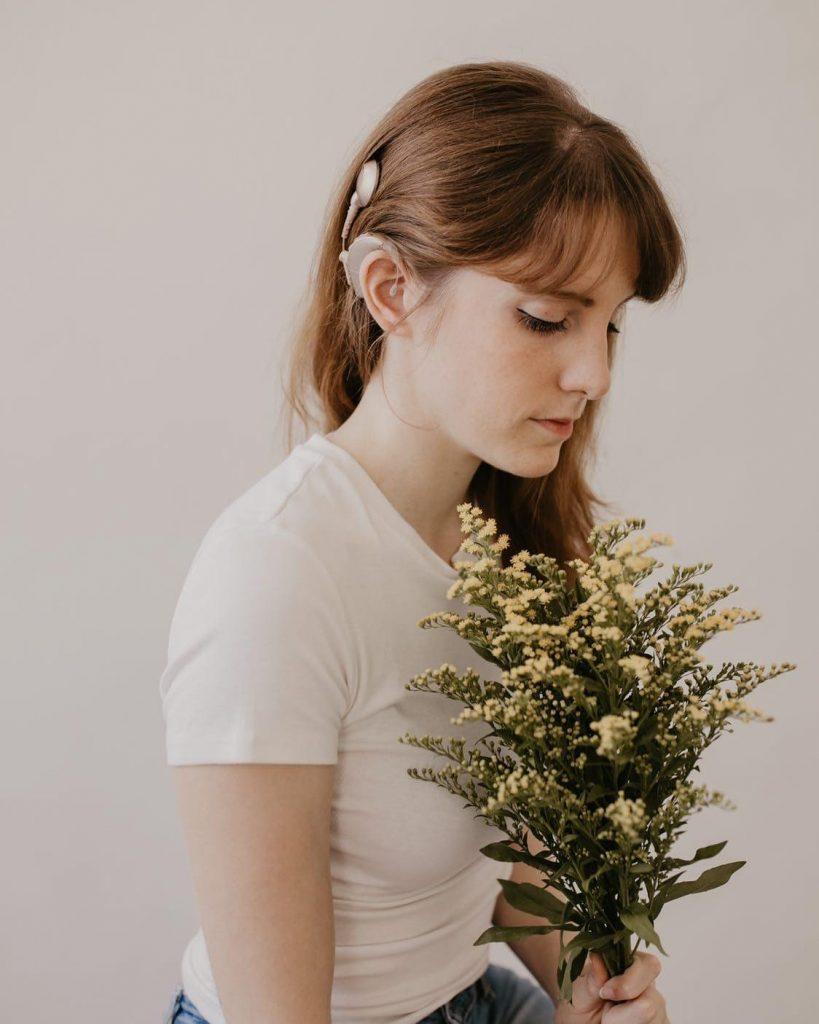 Chiara Pennetta con il suo impianto cocleare bilaterale e un mazzo di fiori in mano